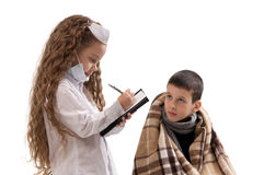 Little girl in nurse costume. Seasonal flu epidemic. Sick sad little boy wrapped in a blanket Stock Photos