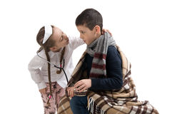 Little girl in nurse costume. Seasonal flu epidemic. Sick sad little boy wrapped in a blanket Stock Photography