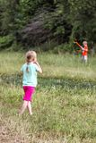 Little girl observing brother having fun with his kite royalty free stock image