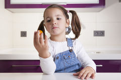 Little girl observing a colorful cherry tomatoe before tasting i. T Stock Photography