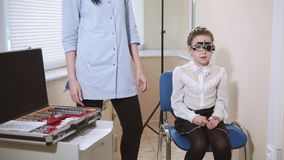 Little girl is in oculist appointment, checking her vision, wearing trial frame. Cute small girlie is sitting on a chair in ophthalmologist office. Doctor is stock video footage