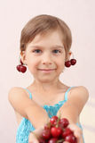 Little girl offering a handful of cherries. Little girl with handful of cherries royalty free stock photos
