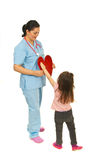 Little girl offering heart to doctor Royalty Free Stock Photos