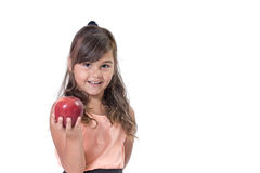 Little girl is offering  a red apple in her hand. Smiling attractive little girl is offering a red apple. Everything is on a white background Royalty Free Stock Photos
