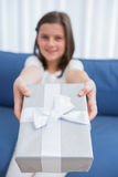 Little girl offering a silver gift Royalty Free Stock Photo