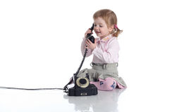 Little girl with old black phone. Stock Images