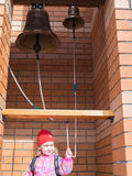 A little girl in old bronze ringing bells. Stock Photography