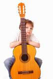 Little girl with an old concert guitar Royalty Free Stock Photos