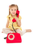 Little girl with old phone sitting on the floor Stock Photos