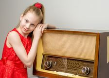 The girl is at the old radio. Stock Photo
