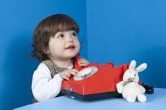Little girl with old red phone. On blue background Royalty Free Stock Image