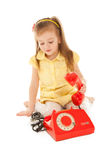 Little girl with old red phone sitting on the floor Royalty Free Stock Photo