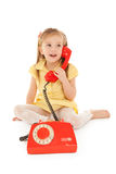Little girl with old red phone sitting on the floor Royalty Free Stock Photos