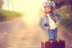 A little girl with an old suitcase Stock Image