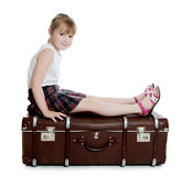 The little girl on old suitcases Stock Image