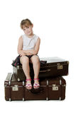 The little girl on old suitcases Stock Photo