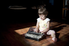 Little girl with old  typewriter. Cute little baby with retro style typewriter Royalty Free Stock Photo