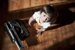 Little girl with old  typewriter. Cute little baby with retro style typewriter Royalty Free Stock Image