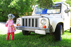 Little girl and old white jeep, child is in front of the car Stock Photos