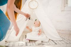 Little girl one year with blue eyes blonde in a lush white dress is pleased and plays in a bright room on background of an Indian Stock Photo