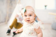 Little girl one year with blue eyes blonde in a lush white dress is pleased and plays in a bright room on background of an Indian Stock Images