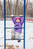 Little girl one year old climbing the ladder outside in winter park playground. Royalty Free Stock Image