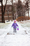 Little girl one year old playing with snow outside in winter park. Royalty Free Stock Images