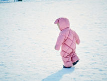 The little girl one year old takes the first steps on the winter park Royalty Free Stock Image
