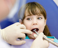 Little girl with open mouth during drilling treatment at the den Stock Image