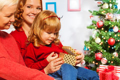 Little girl open presents with mother and granny Royalty Free Stock Photos