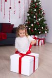 Little girl opening big gift box near Christmas tree at home Stock Images