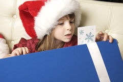 Little girl opening christmas gift. Cheerful cute little girl wearing santa clause hat opening Christmas gift box and reading label message royalty free stock photo