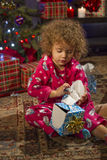 Little girl opening Christmas gift, vertical Stock Photography