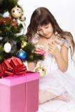 Little girl opening christmas present. Under a Christmas under a Christmas tree Royalty Free Stock Photos
