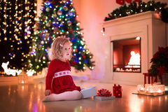 Little girl opening Christmas presents at fire place. Family on Christmas eve at fireplace. Kids opening Xmas presents. Children under Christmas tree with gift royalty free stock image