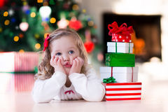 Little girl opening Christmas presents at fire place. Family on Christmas morning at fireplace. Kids opening Xmas presents. Children under Christmas tree with royalty free stock photo