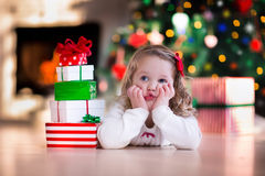 Little girl opening Christmas presents at fire place Stock Images