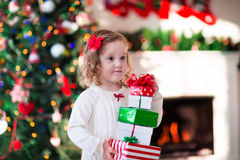 Little girl opening Christmas presents at fire place. Family on Christmas morning at fireplace. Kids opening Xmas presents. Children under Christmas tree with royalty free stock photography