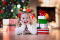 Little girl opening Christmas presents at fire place. Family on Christmas morning at fireplace. Kids opening Xmas presents. Children under Christmas tree with stock photo