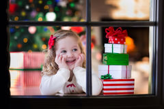 Little girl opening Christmas presents at fire place. Family on Christmas morning at fireplace. Kids opening Xmas presents. Children under Christmas tree with royalty free stock photos