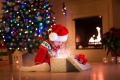 Little girl opening Christmas presents next to a fire place. Family on Christmas eve at fireplace. Kids opening Xmas presents. Children under Christmas tree with royalty free stock photo
