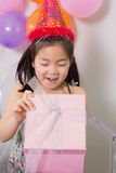 Little girl opening gift box at her birthday party Royalty Free Stock Photos
