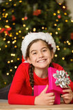 Little girl opening a gift at christmas Stock Image