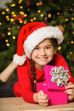 Little girl opening a gift at christmas Royalty Free Stock Photo