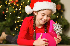 Little girl opening a gift at christmas Royalty Free Stock Photos