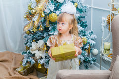 Little girl opening a gift at home in the living room Stock Photography