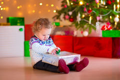 Little girl opening her Christmas present Royalty Free Stock Images
