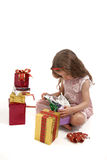 Little girl opening her Christmas presents Stock Images
