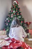 Little girl opening her gifts under Christmas tree Stock Images