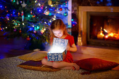 Little girl opening a magical Christmas gift Royalty Free Stock Photos